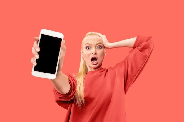 Junge blonde überraschte frau, die auf korallenhintergrund mit smartphone schreit Kostenlose Fotos