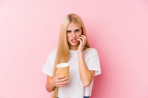 Junge blondine, die beißende fingernägel eines mitnehmerkaffees, nervös und sehr besorgt halten Premium Fotos