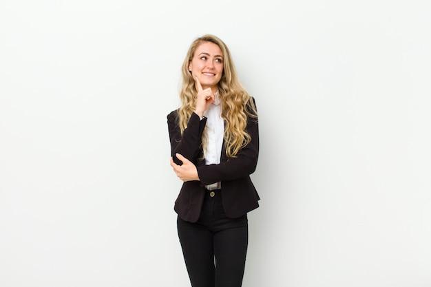 Junge blondine, die glücklich lächeln und träumen oder zweifeln und zur seite auf weißer wand schauen Premium Fotos