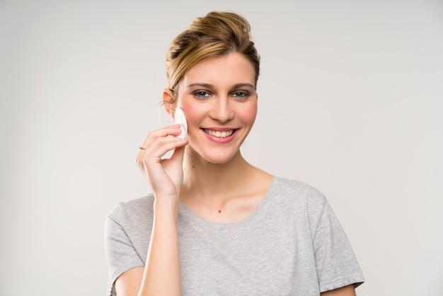 Junge blondine, die make-up von ihrem gesicht mit baumwollauflage entfernen Premium Fotos