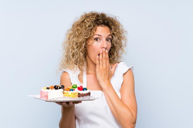 Junge blondine mit dem gelockten haar, das viele verschiedene minikuchen mit überraschungsgesichtsausdruck hält Premium Fotos