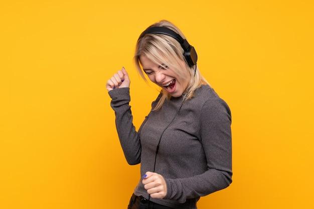 Junge blondine über hörender musik und tanzen der lokalisierten gelben wand Premium Fotos