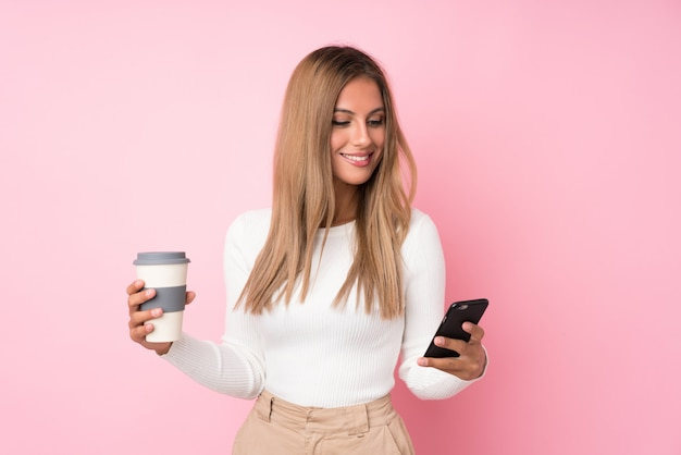 Junge blondine über lokalisiertem rosa haltenem kaffee zum mitnehmen und einem mobile Premium Fotos