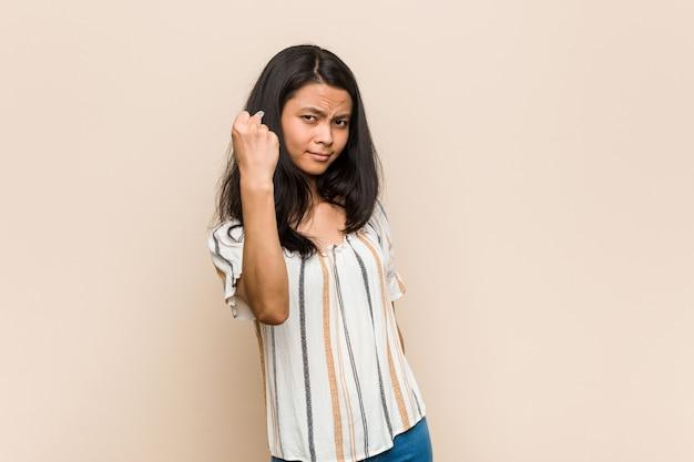 Junge brünette frau, die einen mantel trägt, der faust zeigt Premium Fotos