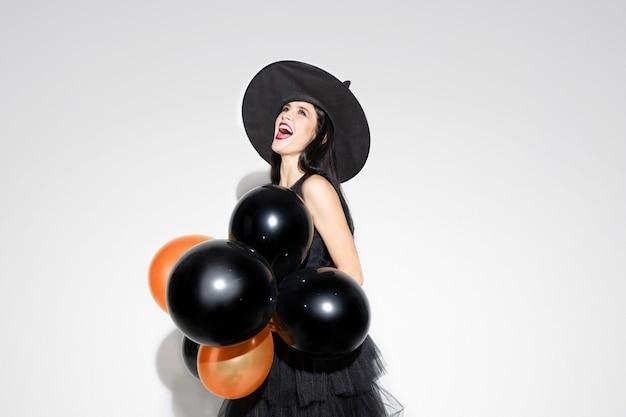 Junge brünette frau im schwarzen hut und im kostüm auf weißem hintergrund. attraktives kaukasisches weibliches modell. halloween, schwarzer freitag, cyber-montag, verkauf, herbstkonzept. copyspace. hält luftballons, beängstigend. Kostenlose Fotos