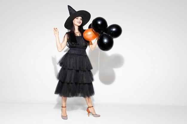 Junge brünette frau im schwarzen hut und im kostüm auf weißem hintergrund. attraktives kaukasisches weibliches modell. halloween, schwarzer freitag, cyber-montag, verkauf, herbstkonzept. copyspace. hält luftballons, lächelt. Kostenlose Fotos