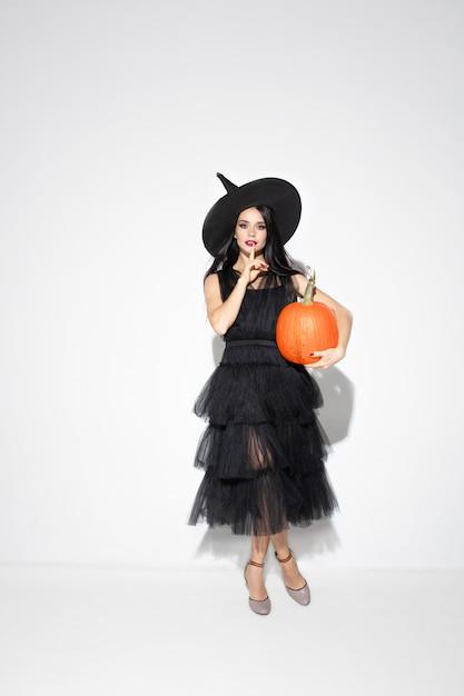 Junge brünette frau im schwarzen hut und im kostüm auf weißem hintergrund. attraktives kaukasisches weibliches modell. halloween, schwarzer freitag, cyber-montag, verkauf, herbstkonzept. copyspace. hält pumpking. Kostenlose Fotos