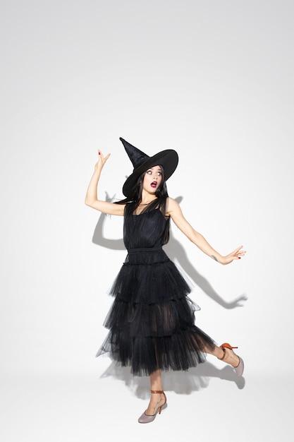 Junge brünette frau im schwarzen hut und im kostüm auf weißem hintergrund. attraktives kaukasisches weibliches modell. halloween, schwarzer freitag, cyber-montag, verkauf, herbstkonzept. copyspace. tanzen, posieren. Kostenlose Fotos