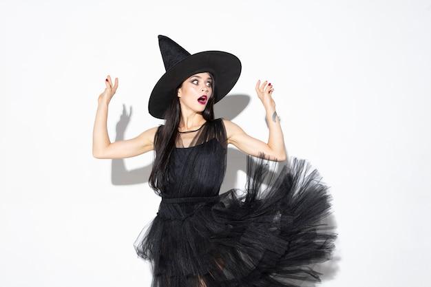 Junge brünette frau im schwarzen hut und im kostüm auf weißem hintergrund. attraktives kaukasisches weibliches modell. halloween, schwarzer freitag, cyber-montag, verkauf, herbstkonzept Kostenlose Fotos