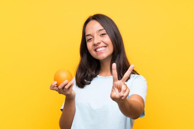 Junge brunettefrau, die eine orange lächelt und siegeszeichen zeigt Premium Fotos