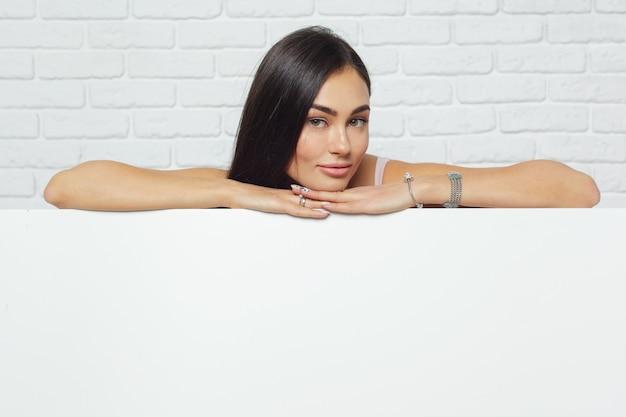 Junge brunettefrau, die großes leeres weißes brett mit kopienraum hält Premium Fotos