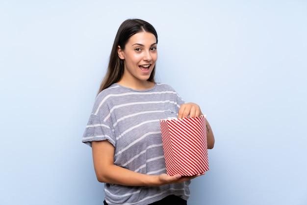 Junge brunettefrau, die popcorn isst Premium Fotos