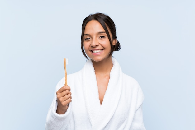 Junge brunettefrau im bademantel, der ihre zähne über dem lokalisierten blau viel lächelt putzt Premium Fotos