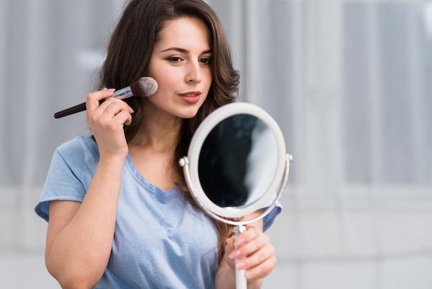 Junge brunettefrau mit der make-upbürste, die im spiegel schaut Kostenlose Fotos