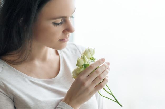 Junge brunettefrau mit weißrosenblumen Premium Fotos