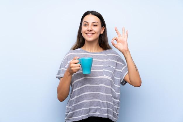Junge brunettefrau über dem lokalisierten blauen hintergrund, der heißen tasse kaffee hält Premium Fotos