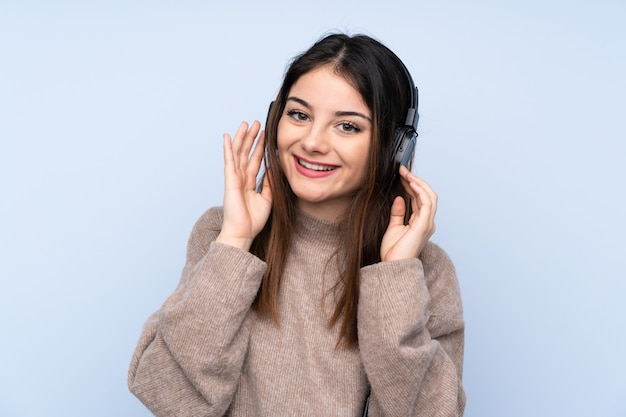 Junge brunettefrau über hörender musik der blauen wand Premium Fotos