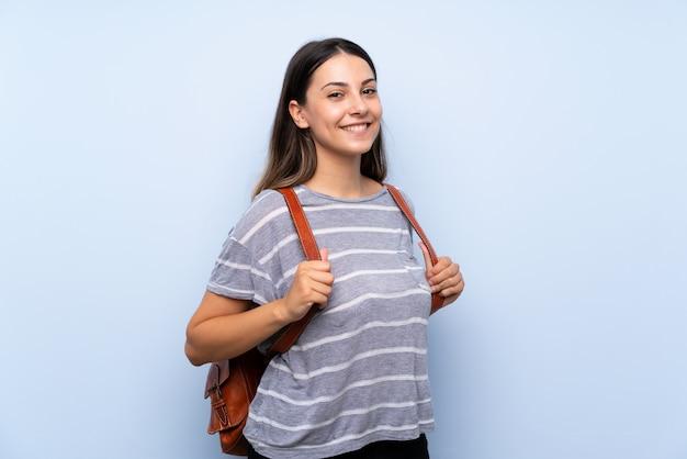 Junge brunettefrau über lokalisierter blauer wand mit rucksack Premium Fotos