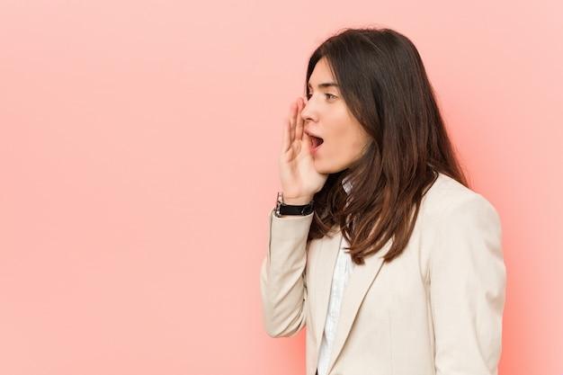 Junge brunettegeschäftsfrau gegen ein rosa, das palme nahe geöffnetem mund schreit und hält. Premium Fotos