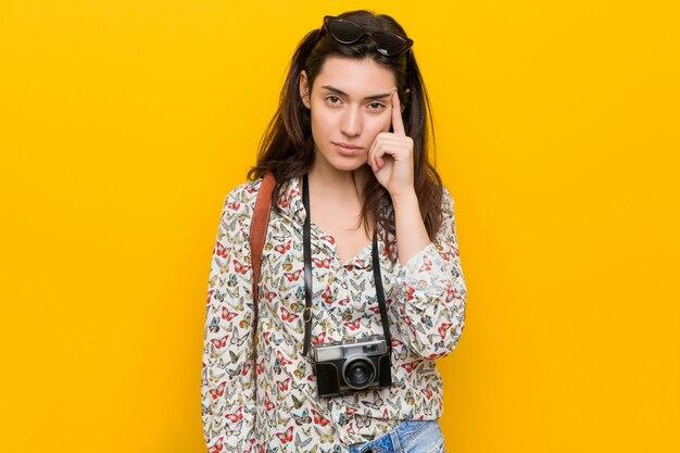 Junge brunettereisendfrau, die tempel mit dem finger, denkend zeigt, konzentrierte sich auf eine aufgabe. Premium Fotos