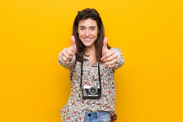 Junge brunettereisendfrau mit den daumen ups, beifall über etwas, unterstützung und respekt. Premium Fotos