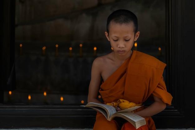 Junge buddhistische anfängermönchlesung, junge buddhistische anfängermönchstudie innerhalb des klosters. asiatischer junger buddhistischer mönch in einem der tempel in thailand. Premium Fotos