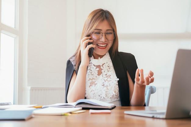 Junge bürofrau, die am handy spricht. Premium Fotos