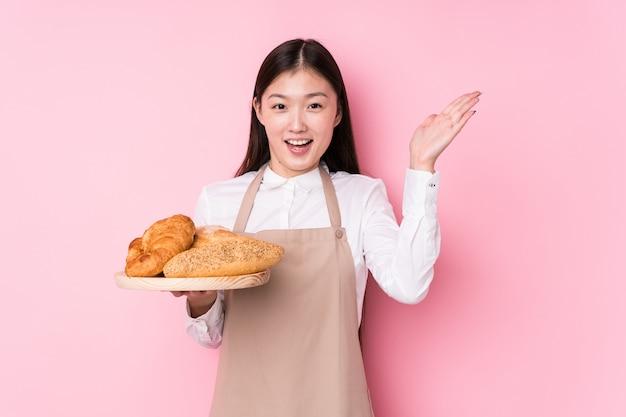Junge chinesische bäckerfrau lokalisiert, eine angenehme überraschung empfangend, aufgeregt und hände anhebend. Premium Fotos