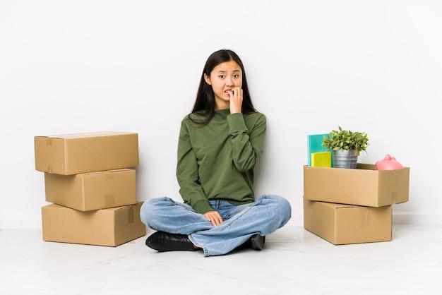 Junge chinesische frau, die auf beißende fingernägel eines neuen hauses, nervös und sehr besorgt umzieht. Premium Fotos