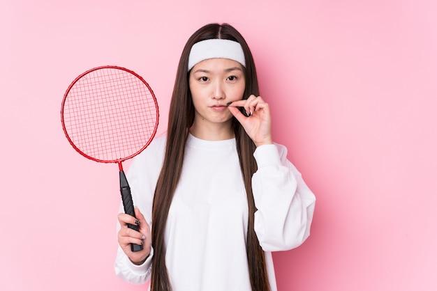 Junge chinesische frau, die das badminton lokalisiert mit den fingern auf den lippen halten ein geheimnis spielt. Premium Fotos