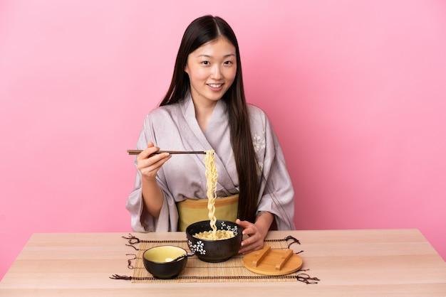 Junge chinesische frau, die kimono trägt und nudeln in
