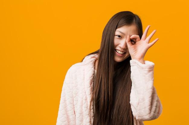 Junge chinesische frau im pyjama aufgeregt, ok geste auf auge zu halten. Premium Fotos