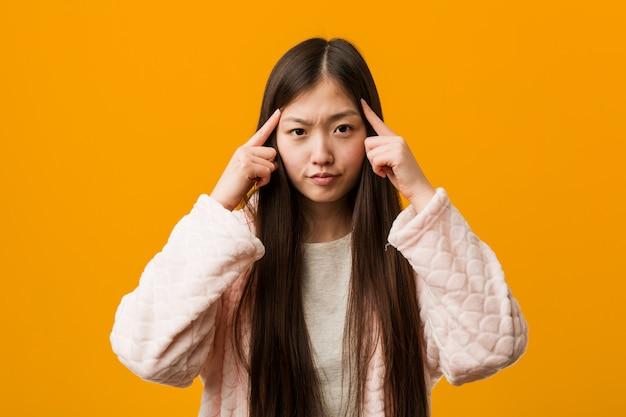 Junge chinesische frau im pyjama konzentrierte sich auf eine aufgabe und hielt ihn die zeigefinger, die kopf zeigen. Premium Fotos