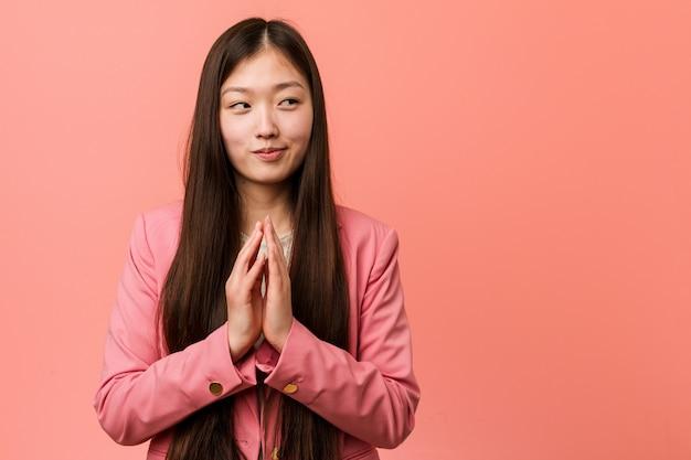 Junge chinesische geschäftsfrau, die den rosa anzug bildet plan im verstand, eine idee gründend trägt. Premium Fotos