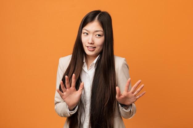 Junge chinesische geschäftsfrau, die jemand zeigt eine geste des ekels zurückweist. Premium Fotos