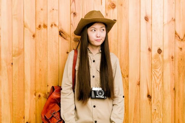 Junge chinesische reisende frau verwirrt, fühlt sich zweifelhaft und unsicher. Premium Fotos