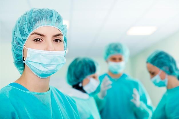 Junge chirurgin mit medizinischem team im rücken vor der operation Kostenlose Fotos