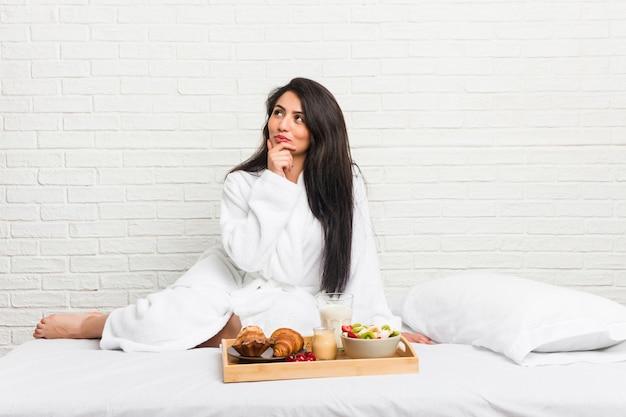 Junge curvy frau, die ein frühstück auf dem bett seitlich schaut mit zweifelhaftem und skeptischem ausdruck nimmt. Premium Fotos
