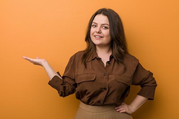 Junge curvy russische frau, die eine kopie auf einer palme zeigt und eine andere hand auf taille hält. Premium Fotos
