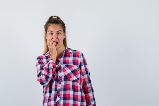 Junge dame beißt ihre nägel in kariertem hemd und sieht aufgeregt aus. vorderansicht. Kostenlose Fotos