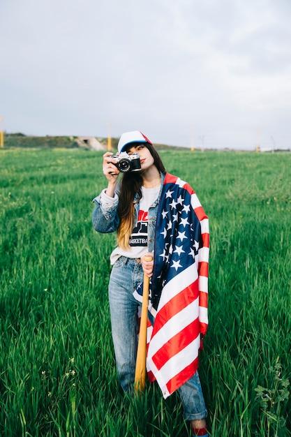 Junge dame, die auf dem gebiet mit amerikanischer flagge bleibt Kostenlose Fotos