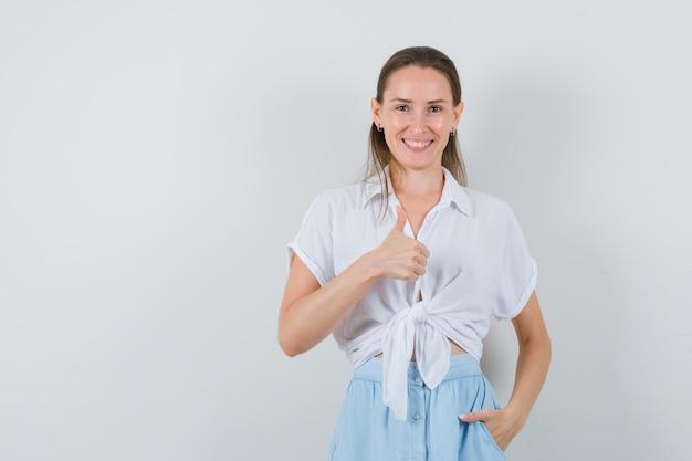Junge dame, die daumen in bluse und rock zeigt und glücklich schaut Kostenlose Fotos