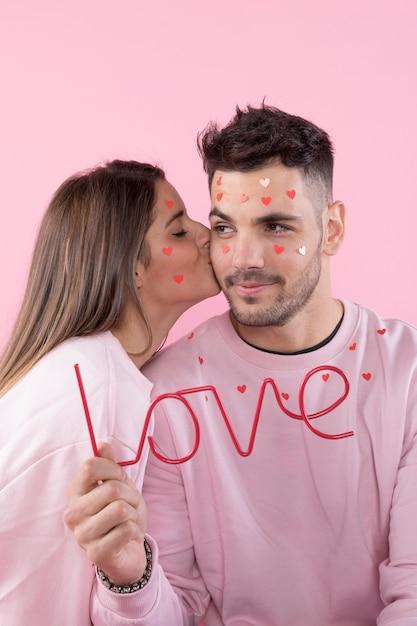 Junge dame, die kerl mit papierherzen auf gesichtern und liebeszeichen küsst Kostenlose Fotos