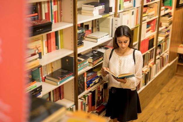 Junge dame, die nahe bücherregal liest Kostenlose Fotos