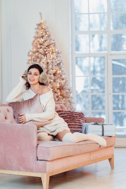 Junge dame im weißen kleid auf dem sofa in der weihnachtszeit Kostenlose Fotos