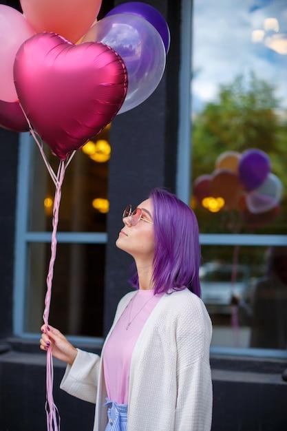 Junge dame mit dem violetten haar in den rosa schauspielen mit den luftballonen, die oben schauen Premium Fotos