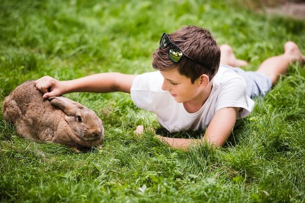 Junge, der auf dem grünen gras liebt sein kaninchen liegt Kostenlose Fotos