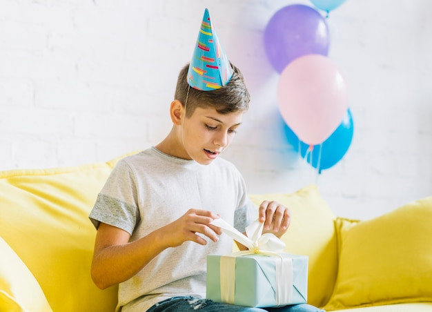 Junge, der auf dem sofa auspackt geburtstagsgeschenk sitzt Kostenlose Fotos