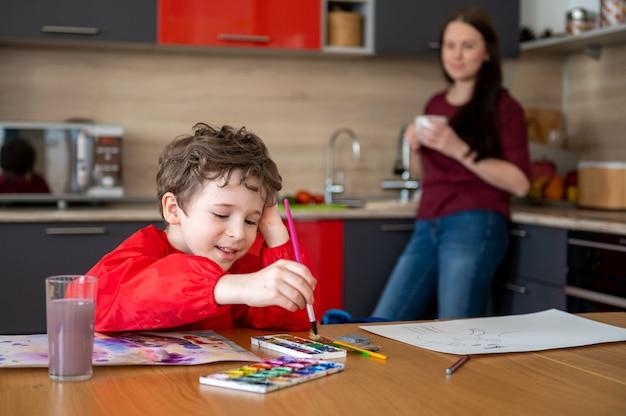 Junge, der auf der küche zeichnet, während mutter tee oder kaffee trinkt Premium Fotos