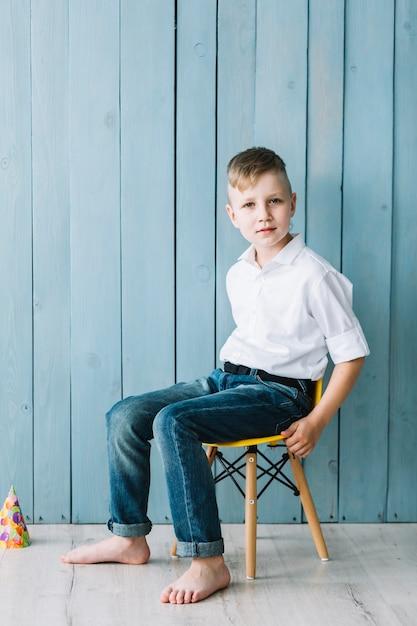 Junge, der auf stuhl während der geburtstagsfeier sitzt Kostenlose Fotos
